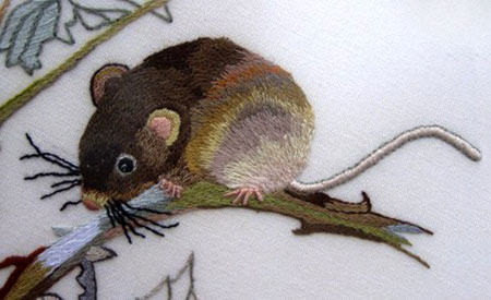 Close up of the detail in a surface embroidery of a mouse